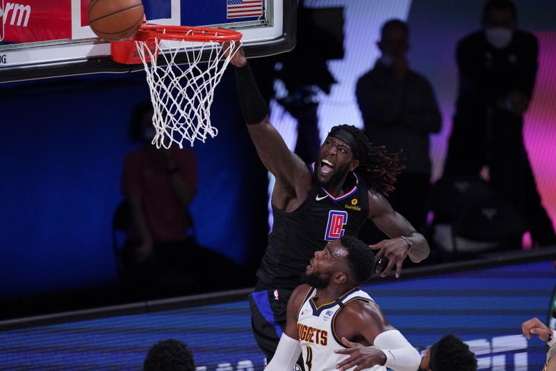 Los Angeles Clippers forward Montrezl Harrell (5) drives to the basket over Denver Nuggets forward Paul Millsap (4) during the first half of an NBA conference semifinal playoff basketball game Tuesday, Sept. 15, 2020, in Lake Buena Vista, Fla. (AP Photo/Mark J. Terrill)