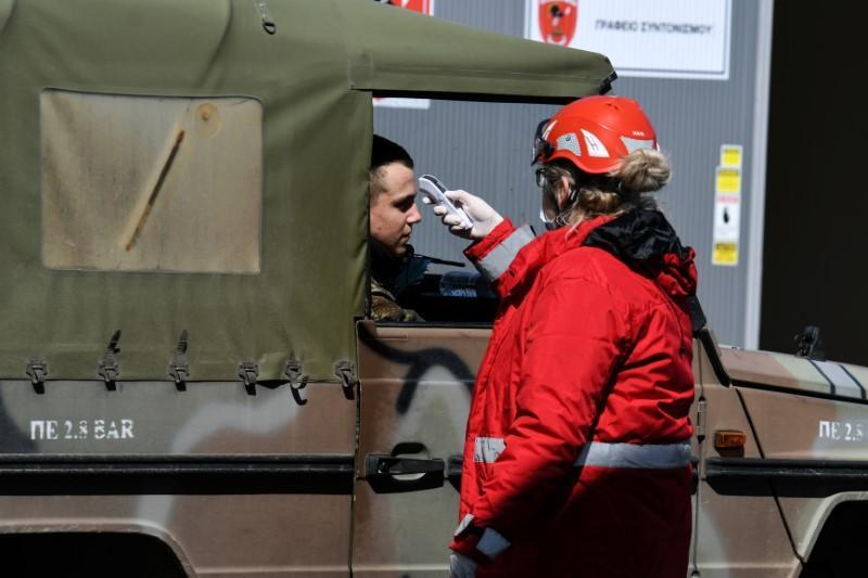 A member of the Hellenic Red Cross checks the temperature of a Greek soldier, as a precaution against the spread of the coronavirus disease (COVID-19), at the Kastanies border crossing area with Turkey's Pazarkule