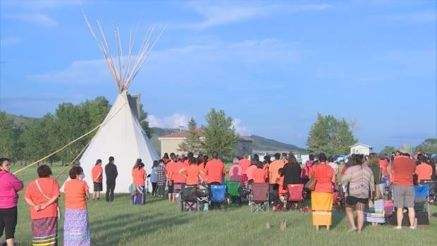 Against the backdrop of a blue prairie sky, a large group of peoplegathered on the Cowessess First Nation on Saturday evening to honour the remains of many Indigenous children in 751 unmarked graves near a former residential school. (Olivier Rouquairol Jodouin/CBC - image credit)
