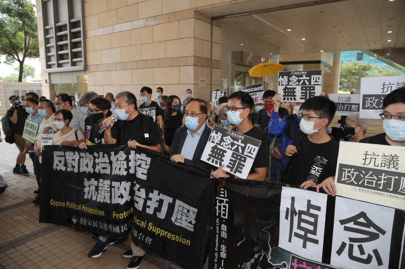 """Various of groups of pro-democracy activists holding banners and placards, arrive at a court in Hong Kong, Tuesday, Sept. 15, 2020. Prominent activists Jimmy Lai and Joshua Wong were among more than two dozen activists appearing in court after being charged of participating in unlawful assembly. They were charged for joining a vigil last June 4 to commemorate the anniversary of the 1989 Tiananmen crackdown. While the event has been held every year, authorities did not grant permission for the gathering this year citing concerns over the spread of coronavirus. The placards and banners read """"Innocent to mourn June 4th"""" and """"Against political prosecution."""" (AP Photo/Kin Cheung)"""