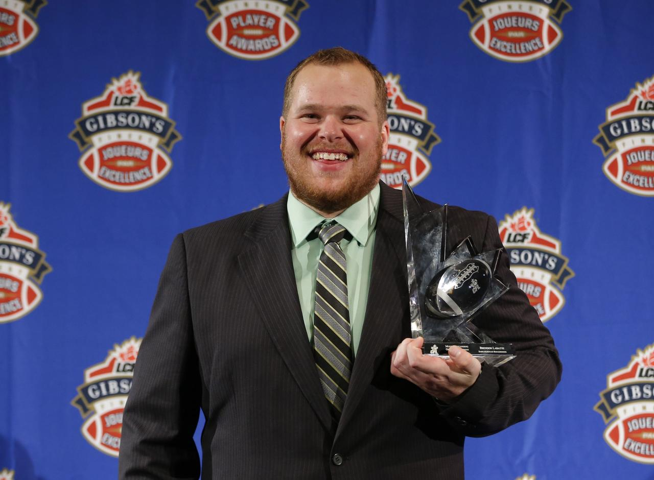 Brendon Labatte of the Saskatchewan Roughriders holds the trophy after being named the CFL's Most Outstanding Offensive Lineman at the CFL Player Awards in Regina, Saskatchewan, November 21, 2013. REUTERS/Todd Korol (CANADA - Tags: SPORT FOOTBALL)