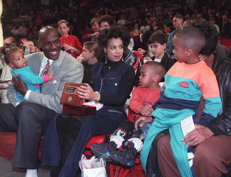 Retired Chicago Bulls star Michael Jordan, left, holds his daughter Jasmine while his wife Juanjita and sons, Marcus and Jeffrey, right, look on following presentation of the 1993 NBA Championship rings prior to the Bulls home opener against the Miami Heat Nov. 6,1993, at Chicago Stadium.
