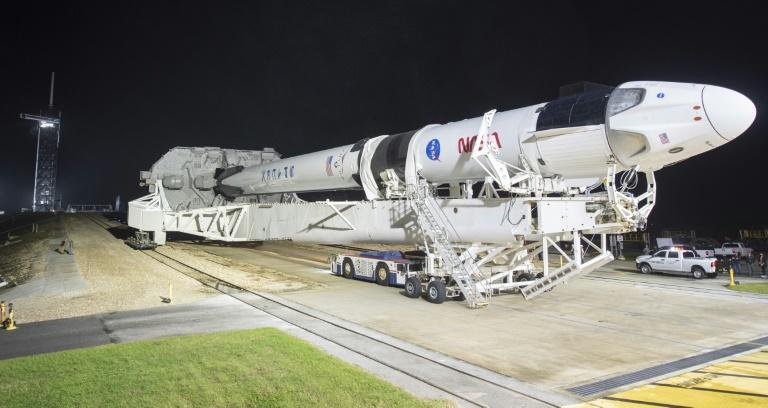 A SpaceX Falcon 9 rocket with the company's Crew Dragon spacecraft onboard is rolled out at the Kennedy Space Center