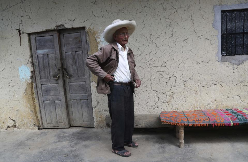 Ireño Castillo, the father of Free Peru party presidential candidate Pedro Castillo, stands inside his home in Puna, Peru, Friday, April 16, 2021. Ireño's rural teacher son, who has proposed rewriting Peru's constitution and deporting all immigrants living in the country illegally who commit crimes, will face rival candidate Keiko Fujimori in the June 6 presidential run-off election. (AP Photo/Martin Mejia)