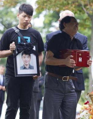 Dirang Lin, father of slain student Jun Lin holds the ashes at his son's gravesite during funeral services in Montreal, July 26, 2012.