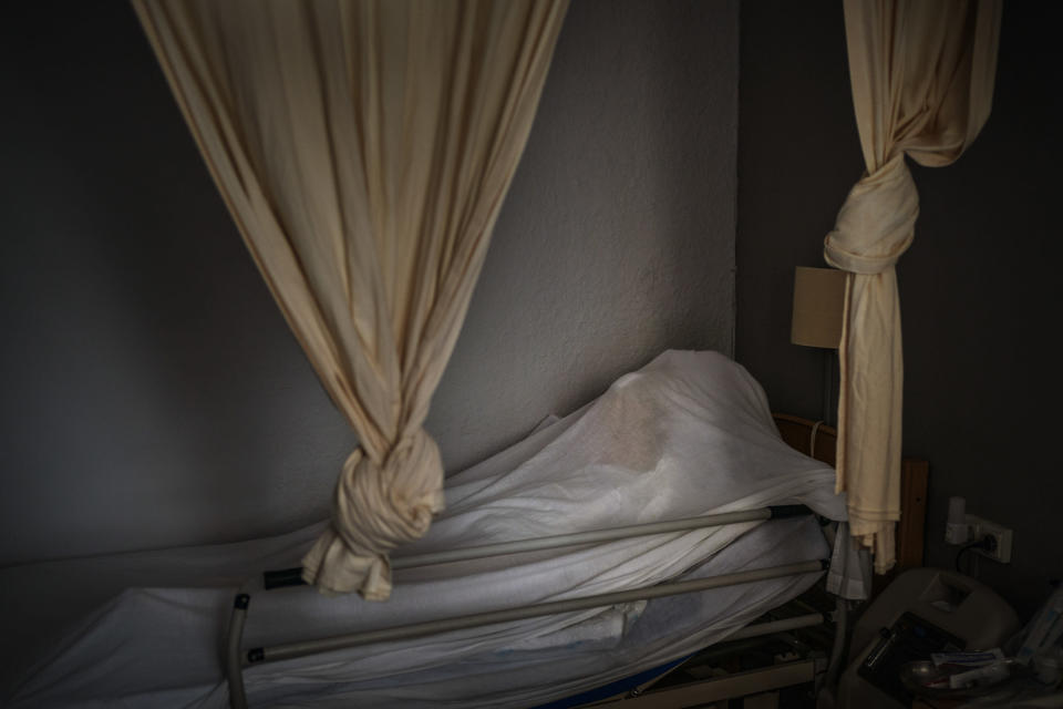 The body of an elderly person who died of COVID-19 is covered with a sheet on her bed in a nursing home in Barcelona, Spain, Nov. 13, 2020. The image was part of a series by Associated Press photographer Emilio Morenatti that won the 2021 Pulitzer Prize for feature photography. (AP Photo/Emilio Morenatti)