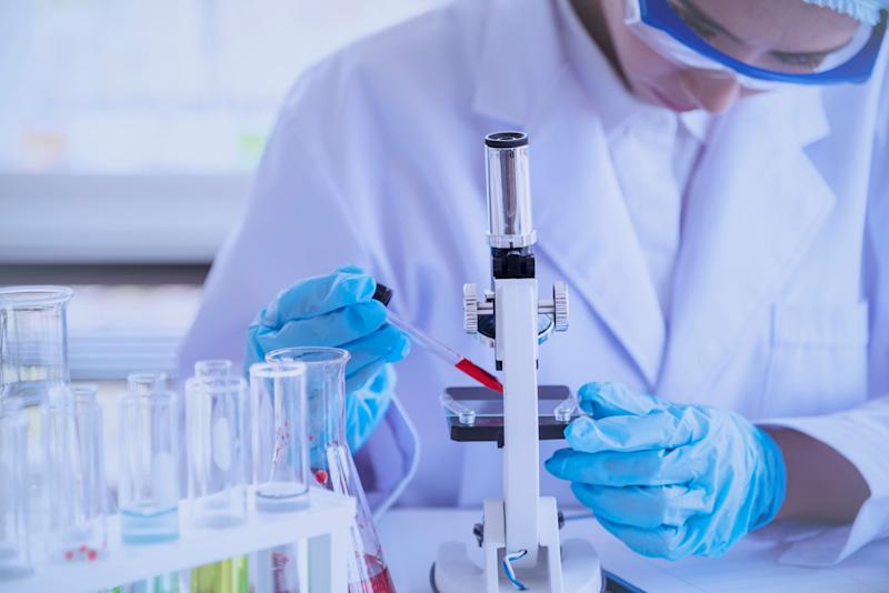 Scientific covid-19 virus antibody sample in laboratory research experiment biotech make cultivate vaccine against virus. Scientist look at microscope, science test tube analyse Chemistry laboratory (Photo: howtogoto via Getty Images)