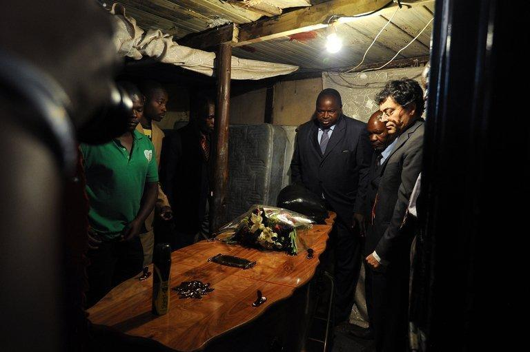 Josehp Macia (C), father of Mido Macia, looks at his son's coffin at his home in Daveyton, on March 8, 2013. Mourners in Mozambique gathered on Saturday for the funeral of Macia who died in police custody in South Africa after officers cuffed him to their van and dragged him through the streets