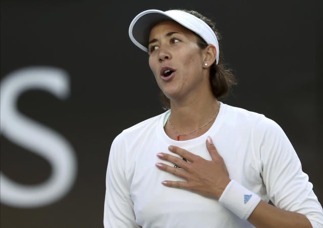 Spain's Garbine Muguruza celebrates after defeating Shelby Rogers of the U.S. in their first round singles match at the Australian Open tennis championship in Melbourne, Australia, Tuesday, Jan. 21, 2020. (AP Photo/Lee Jin-man)