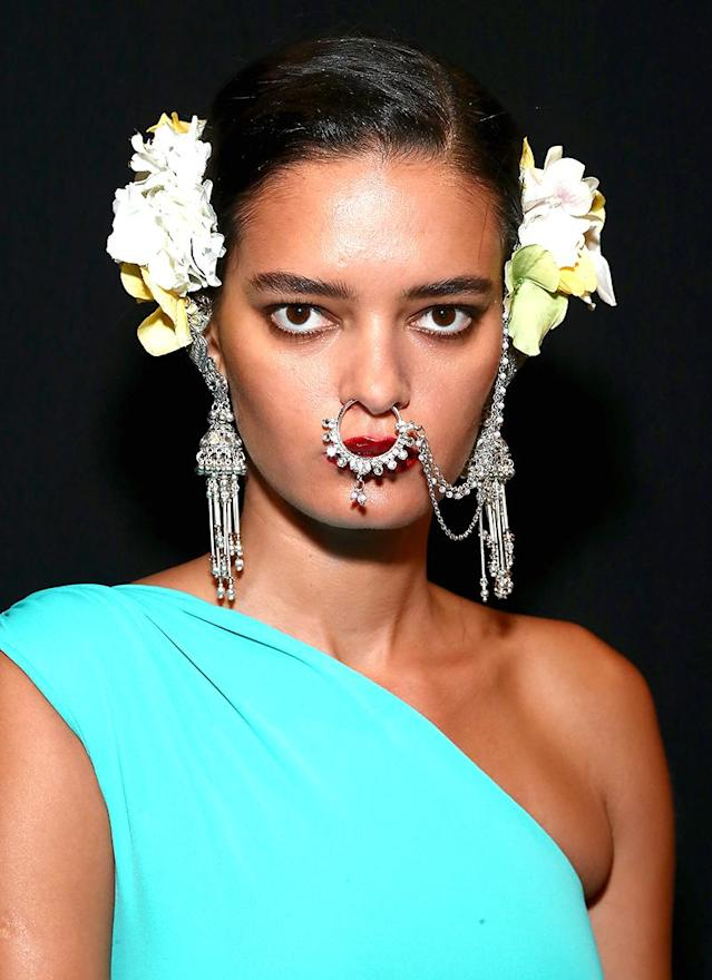 <p>Naeem Khan models sported oversized septum jewelry adorning a classic dark red lip shade. (Photo: Getty Images) </p>