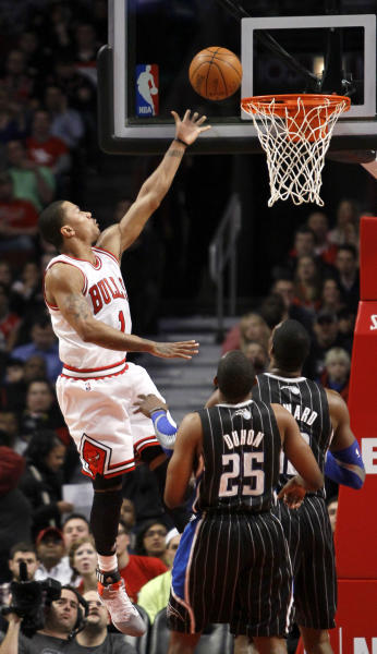 Chicago Bulls guard Derrick Rose (1) drives to the basket past Orlando Magic's Chris Duhon and Dwight Howard during the first half of an NBA basketball game Thursday, March 8, 2012, in Chicago. (AP Photo/Charles Rex Arbogast)