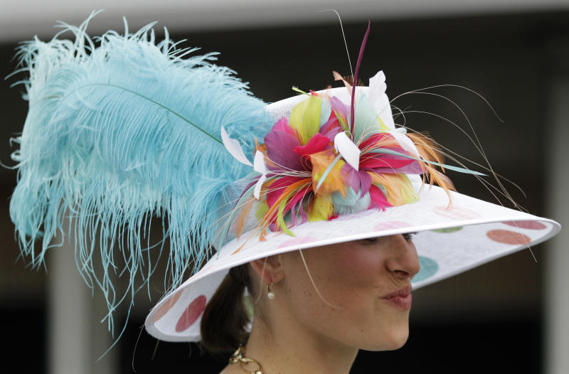 A spectator wears a fancy hat through the paddock area before the 138th Kentucky Derby horse race at Churchill Downs Saturday, May 5, 2012, in Louisville, Ky. (AP Photo/Mark Humphrey)