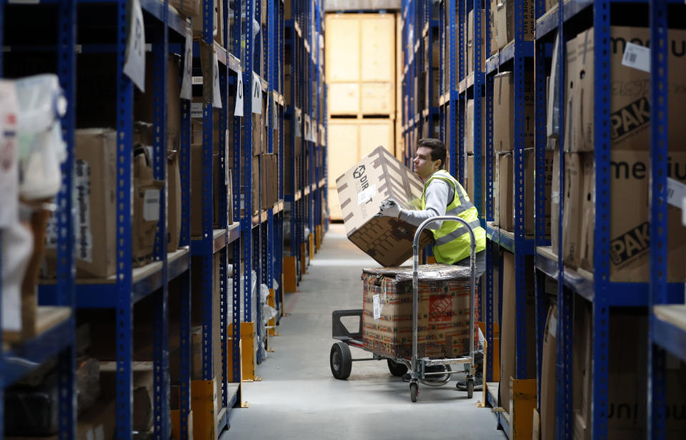 Lovespace warehouse worker Pawel Mazur unloads boxes from a trolley to place them into their allocated zones at the warehouse in Dunstable, England Monday, Jan. 14, 2019. Lovespace, which collects boxes from customers, stores them and then returns the goods when needed, says revenue from businesses doubled over the past year as enterprises large and small began stockpiling inventory because of concerns they will be cut off from suppliers if Britain leaves the European Union without an agreement on future trading relations. (AP Photo/Alastair Grant)