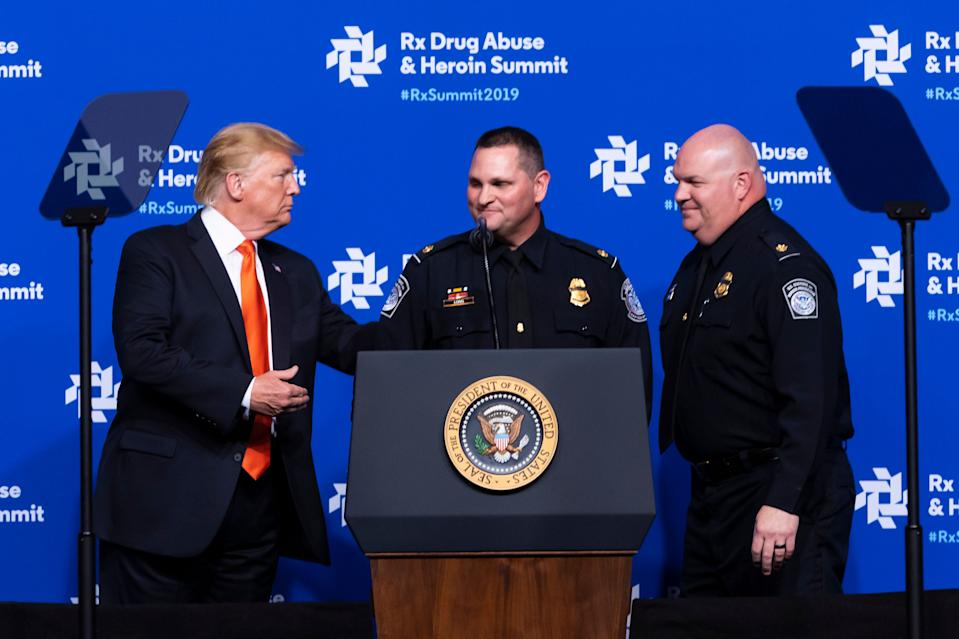 President Donald Trump, left, introduces Customs and Border Patrol officers Long and Noble to speak during the RX Drug Abuse & Heroin Summit, Wednesday, April 24, 2019 in Atlanta. The President was on hand to provide an update on the nation's opioid epidemic to elected leaders and health and law enforcement officials, about what he has called a national health emergency due to an estimated 2 million people whom are addicted to the drugs. (AP Photo/John Amis)