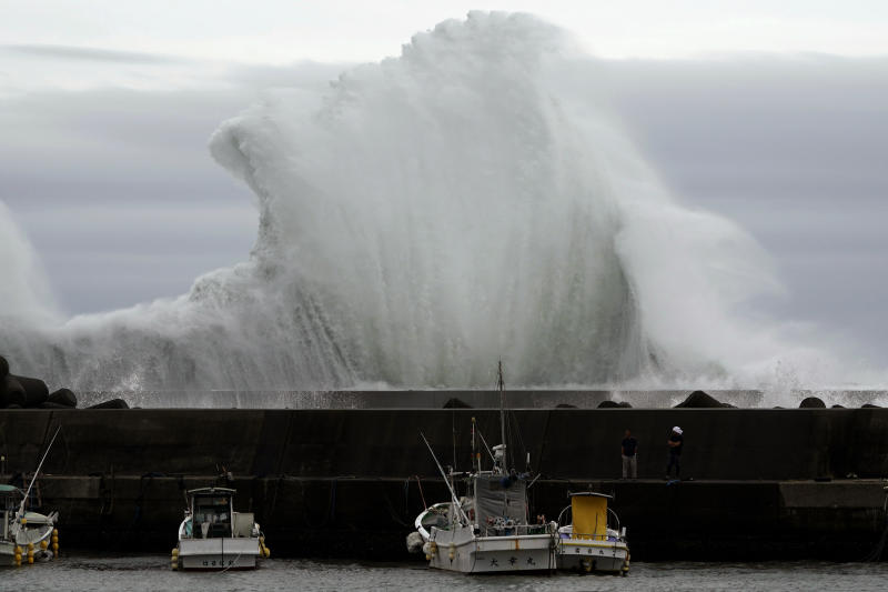 Men look at fishing boats as surging waves hit against the breakwater while Typhoon Hagibis approaches at a port in town of Kiho, Mie Prefecture, Japan Oct. 11, 2019. A powerful typhoon is advancing toward the Tokyo area, where torrential rains are expected this weekend. (Photo: Toru Hanai/AP)