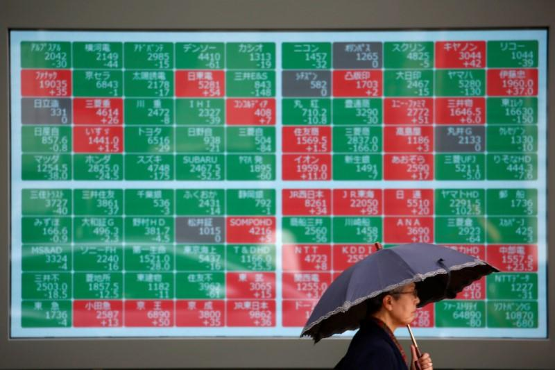 FILE PHOTO: A passerby walks past in front of a stock quotation board outside a brokerage in Tokyo, Japan, May 10, 2019. REUTERS/Issei Kato
