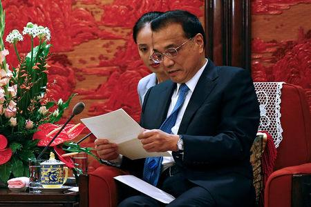 FILE PHOTO:  Chinese Premier Li Keqiang looks at a letter given by Malaysia's Prime Minister Mahathir Mohamad during a meeting with Malaysia's new government advisor Daim Zainuddin at the Zhongnanhai Leadership Compound in Beijing
