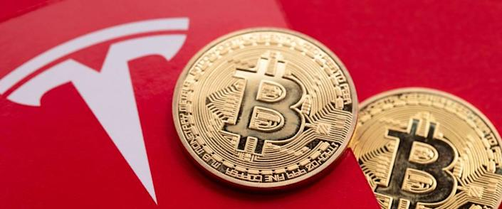 Bitcoin cryptocurrency on a Tesla electric vehicle logo