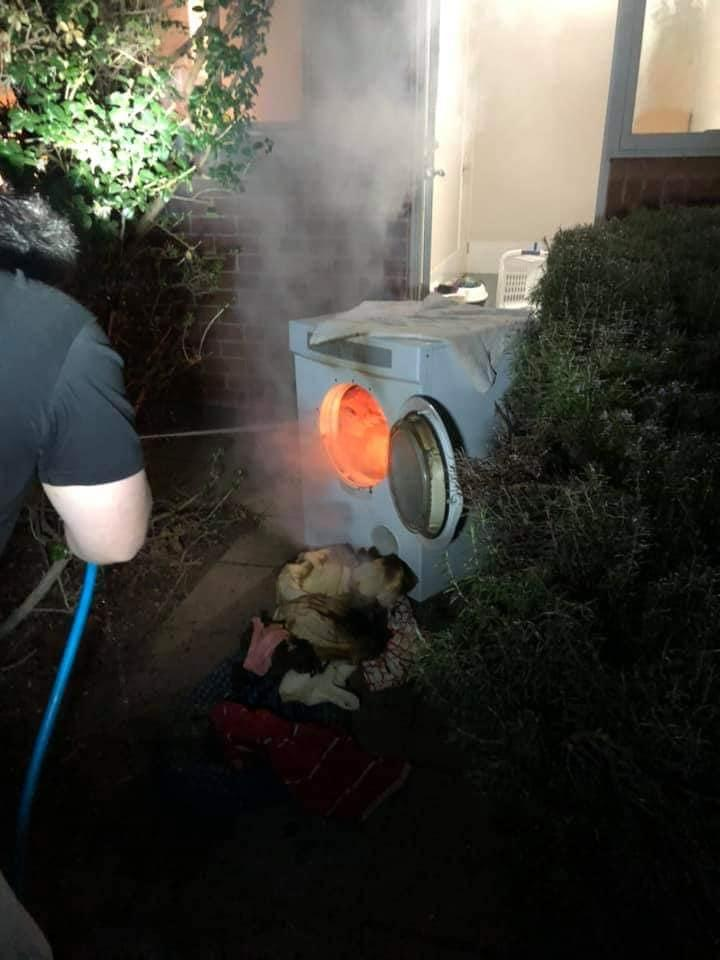 A man douses flames in a clothes dryer with a garden hose at the Murrumbateman home.