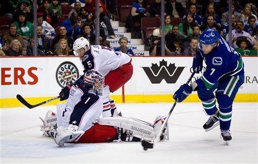 Vancouver Canucks' David Booth, right, scores a goal against Columbus Blue Jackets goalie Steve Mason as Aaron Johnson (5) defends during the first period of an NHL hockey game in Vancouver, British Columbia, on Saturday, March 17, 2012. (AP Photo/The Canadian Press, Darryl Dyck)