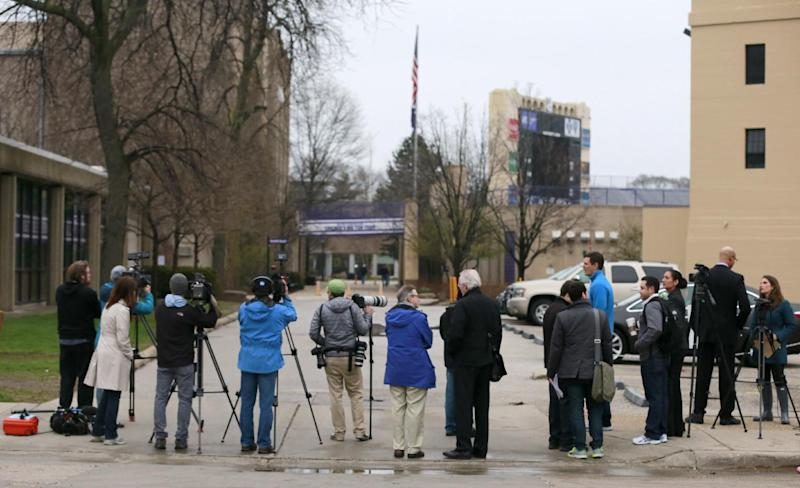 Reporters and photographers between Ryan Field, right, and McGaw Hall, left, where voting is taking place by Northwestern football players on the student athlete union question Friday, April 25, 2014, in Evanston, Ill. Northwestern football players cast secret ballots Friday in an on-campus hall adjacent to their home stadium on whether to form the nation's first union for college athletes. (AP Photo/Charles Rex Arbogast)