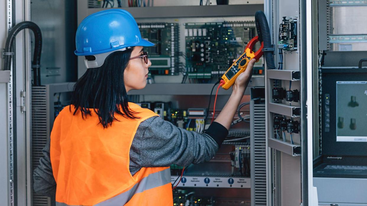Young woman industrial service electrician engineer wearing protective vest and blue technician helmet testing and checking fridge electric voltage with digital multimeter electric measurement instrument a control panel fuse box in boiler energy control room of modern thermal or nuclear power plant electric energy station.