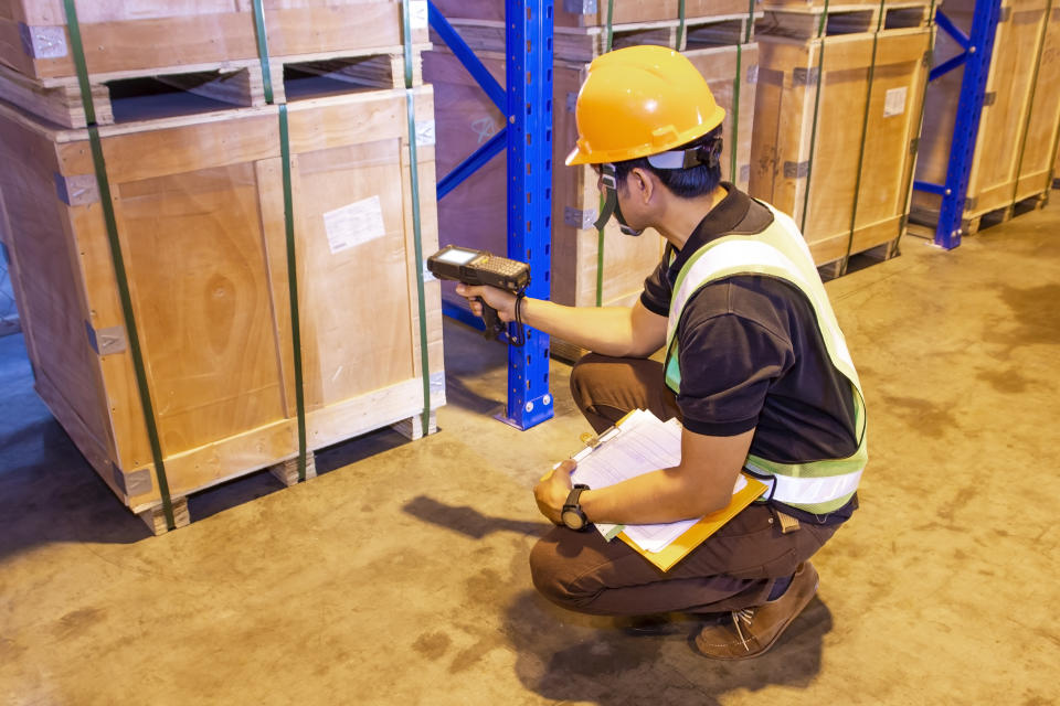 warehouse inventory management, worker in uniform hand holding bar code scanner with scanning on label of cargo pallet.