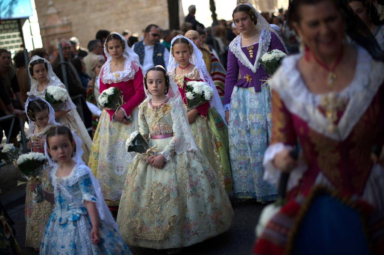 VALENCIA, SPAIN - MARCH 18:  Falleras dressed up in traditonal costume prepare to present flowers to Saint Mary on March 18, 2013 in Valencia, Spain. The Fallas festival, which runs from March 15 until March 19, celebrates the arrival of spring with fireworks, fiestas and bonfires made from large ninots (puppets).  (Photo by David Ramos/Getty Images)