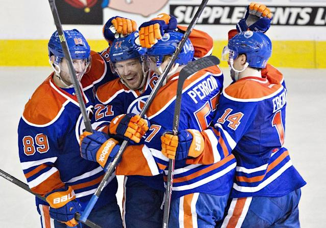 Edmonton Oilers' Sam Gagner (89), Andrew Ference (21), David Perron (57) and Jordan Eberle (14) celebrate a goal in overtime against the Anaheim Ducks during an NHL hockey game in Edmonton, Alberta, on Friday, March 28, 2014. (AP Photo/The Canadian Press, Jason Franson)