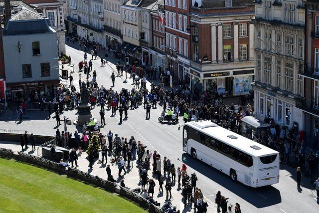 Police hold back the crowds as a coach arrives outside St George's Chapel