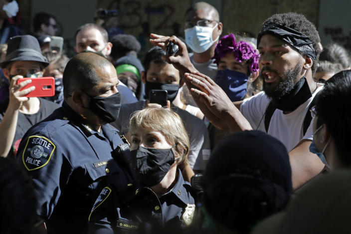 """A protester, right, who did not give his name talks with Seattle Police assistant chiefs Adrian Diaz, left, and Deanna Nollette, center, Thursday, June 11, 2020, inside what is being called the """"Capitol Hill Autonomous Zone"""" in Seattle. The officers were attempting to walk to the police department's East Precinct building, which has been boarded up and abandoned except for a few officers inside, but the protester, in a move that angered some other protesters, said he would walk with the officers to a side entrance of the precinct rather than have them walk directly through a crowd of angry protesters. Following days of violent confrontations with protesters, police in Seattle have largely withdrawn from the neighborhood, where protesters have created a festival-like scene. (AP Photo/Ted S. Warren)"""