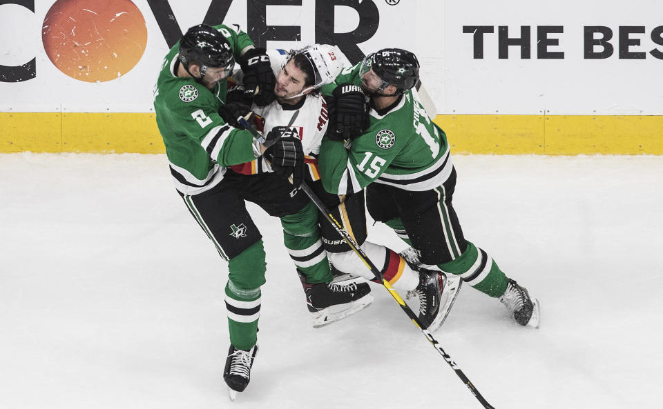 Calgary Flames' Sean Monahan (23) is checked by Dallas Stars' Jamie Oleksiak (2) and Blake Comeau (15) during the third period of a first round NHL Stanley Cup playoff hockey series in Edmonton, Alberta, on Thursday, Aug. 13, 2020. (Jason Franson/The Canadian Press via AP)