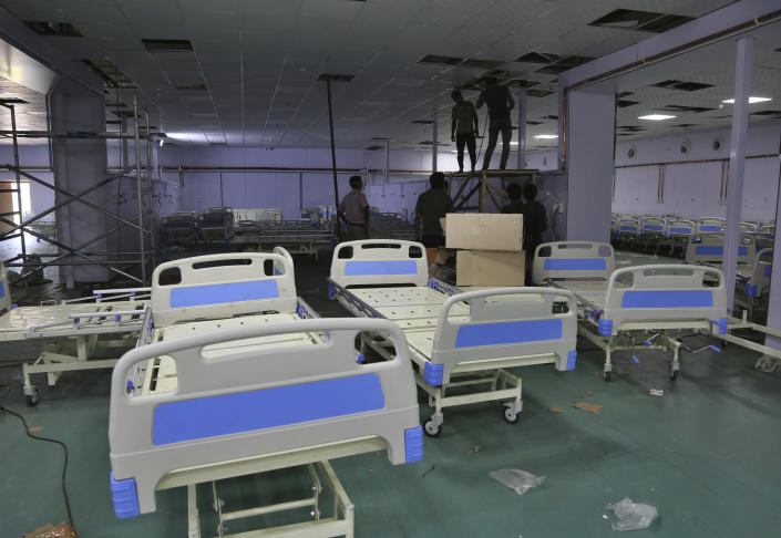 Indian laborers work during the setting up of a temporary 500 bedded COVID-19 hospital by the Defence Research and Development Organization in Jammu, India, Monday, May 24, 2021. India crossed another grim milestone Monday of more than 300,000 people lost to the coronavirus as a devastating surge of infections appeared to be easing in big cities but was swamping the poorer countryside. (AP Photo/Channi Anand)