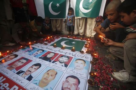 Children light candles in front of a poster with pictures of the members of Airport Security Force (ASF) who were killed on Sunday's Taliban attack on Jinnah International Airport, to commemorate them, in Karachi June 11, 2014. REUTERS/Athar Hussain
