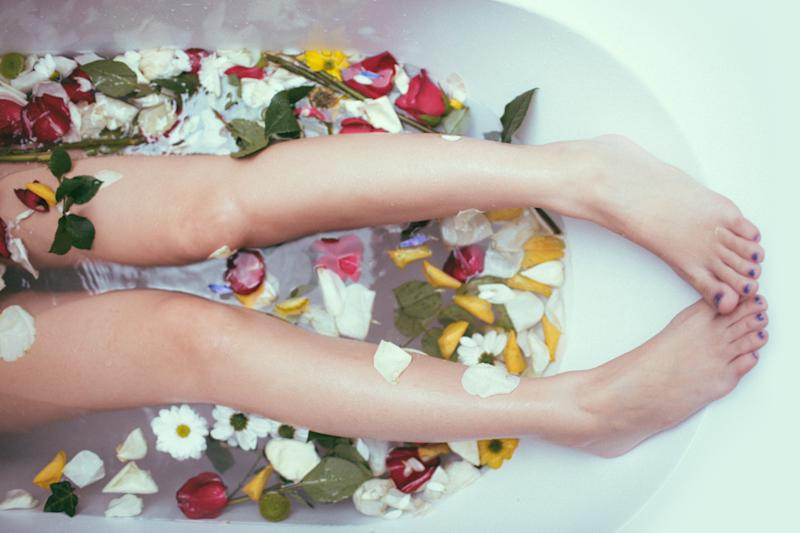 Girl relaxing in bath with flowers