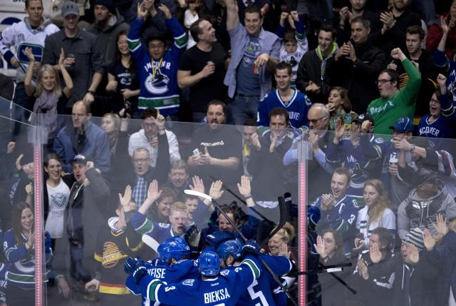 Vancouver Canucks center Mike Santorelli (25) celebrates his goal against the St. Louis Blues with his teammates during the third period of NHL action in Vancouver, British Columbia Friday, Jan. 10, 2014. (AP Photo/The Canadian Press, Jonathan Hayward)