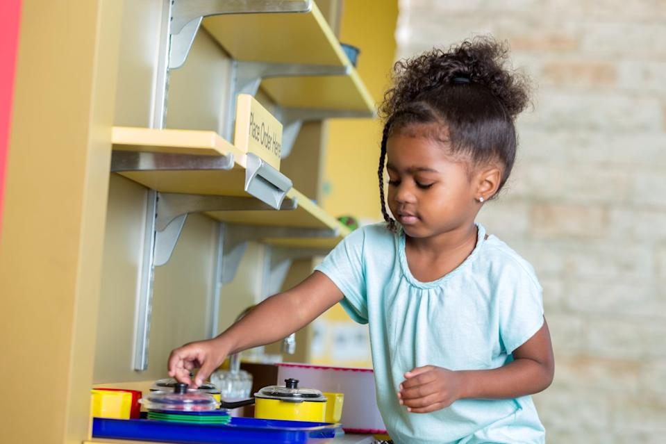 "<p>The third Montessori tool we use is making child-safe items easily accessible to our little one. In her room, she has open low shelving with <a href=""https://www.popsugar.com/family/educational-toys-for-toddlers-46829240"" class=""link rapid-noclick-resp"" rel=""nofollow noopener"" target=""_blank"" data-ylk=""slk:toys"">toys</a> she can access on her own whenever she wants. The shelves are kept tidy and uncluttered, and every two weeks, I rotate out the toys to keep her interested in engaging with ""new"" old toys or items. We also keep her eating utensils, her dishes, and towels in the lowest drawer and cabinet in our kitchen. This allows her to gather her appropriate supplies before we eat together and access a towel if there's a spill. Doing simple shifts like this in your household can offer your child more independence and gives them yet another Montessori activity to engage in throughout the day - which can make your life a bit easier.</p>"