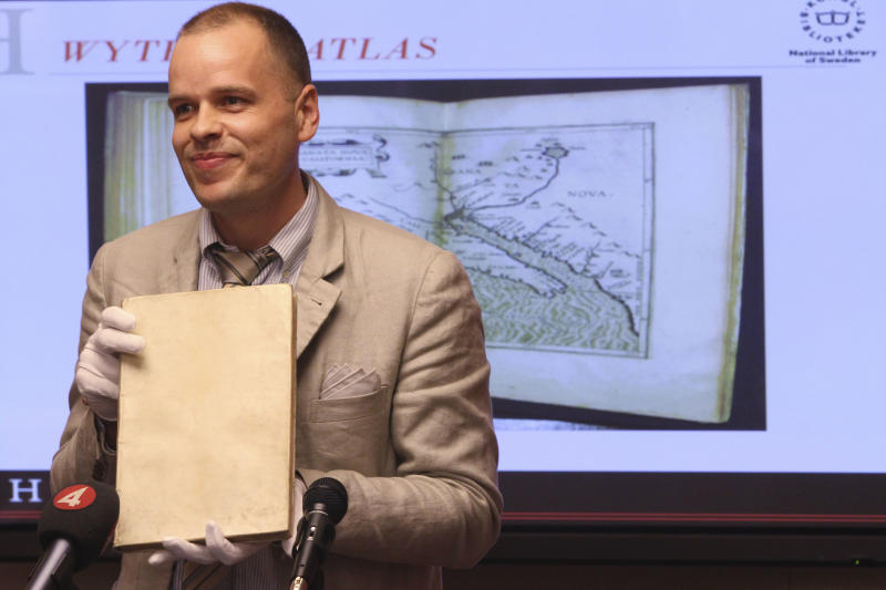 Royal Library's map librarian, Greger Bergvall, holds the Wytfliet Atlas during a news conference, Wednesday, June 27, 2012 in New York. The Wytfliet Atlas stolen a decade ago from the Royal Library of Sweden has been recovered in New York. (AP Photo/Mary Altaffer)