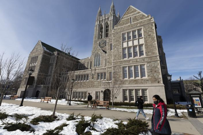 Students walk on the Boston College campus, Wednesday, Feb. 17, 2021, in Boston. (AP Photo/Michael Dwyer)
