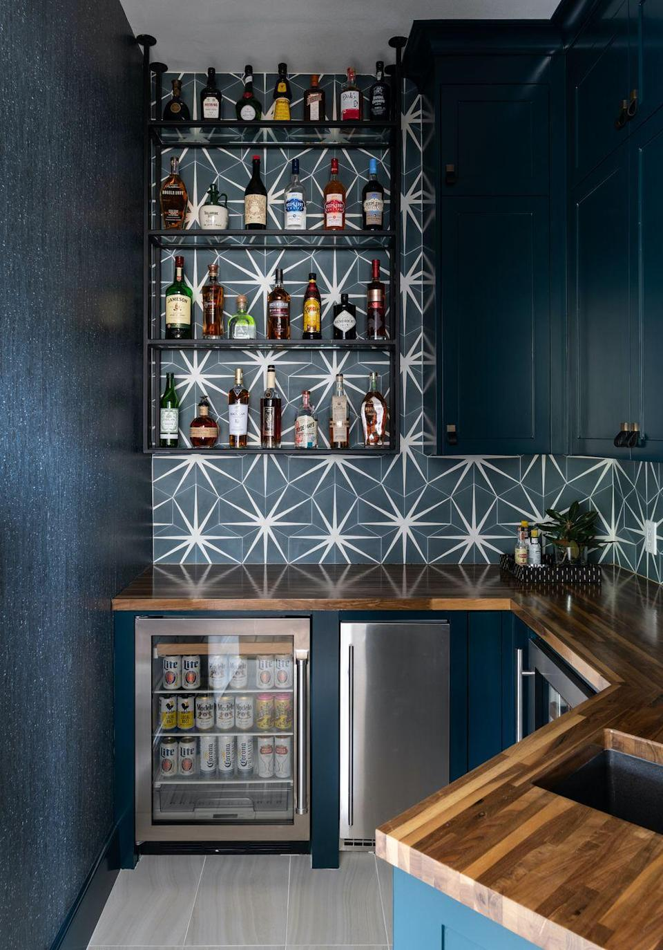 """<p>Instead of adding a backsplash to your <a href=""""https://www.elledecor.com/design-decorate/room-ideas/a34585665/home-bar-design-2020/"""" rel=""""nofollow noopener"""" target=""""_blank"""" data-ylk=""""slk:home bar"""" class=""""link rapid-noclick-resp"""">home bar</a>, take a cue from designer <a href=""""https://traciconnellinteriors.com/"""" rel=""""nofollow noopener"""" target=""""_blank"""" data-ylk=""""slk:Traci Connell"""" class=""""link rapid-noclick-resp"""">Traci Connell</a> and opt for a statement-making wallpaper.</p><p><em>Harmony Navy Wallpaper, $120<br></em><a class=""""link rapid-noclick-resp"""" href=""""https://www.grahambrown.com/us/harmony-navy-wallpaper/107587-master.html"""" rel=""""nofollow noopener"""" target=""""_blank"""" data-ylk=""""slk:Shop the Look"""">Shop the Look</a></p>"""