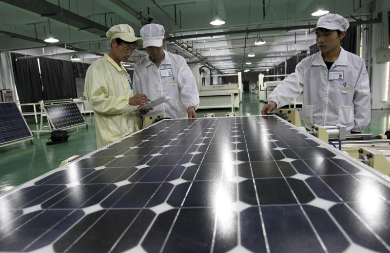 In this photo taken Wednesday March 21, 2012, Chinese workers examine solar panels at a manufacturer of photovoltaic products in Huaibei in central China's Anhui province. China's government on Friday, May 18, 2012, rejected a U.S. antidumping ruling against its makers of solar power equipment and Chinese manufacturers warned proposed punitive tariffs might hurt efforts to promote clean energy. (AP Photo) CHINA OUT