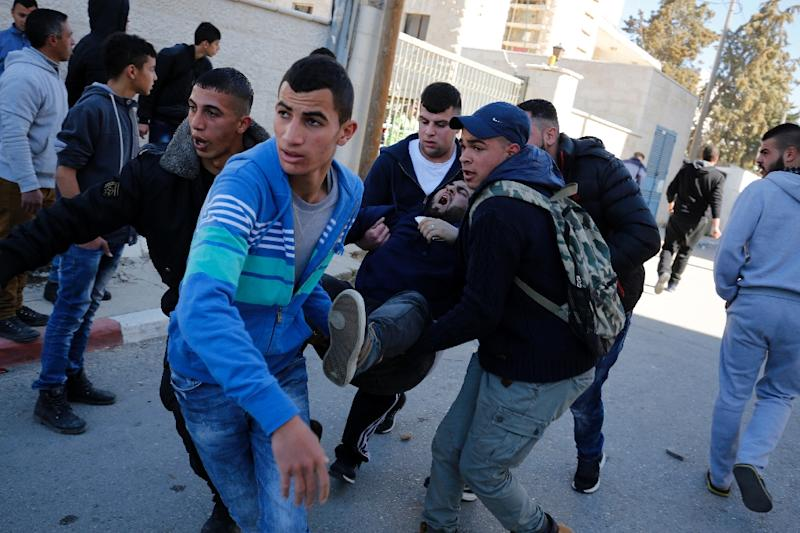 An injured Palestinian man is carried away in the al-Amari Palestinian refugee camp, near the West Bank city of Ramallah, after clashes with Israeli soldiers that erupted after they entered the camp early in the morning on February 15, 2015 (AFP Photo/Abbas Momani)