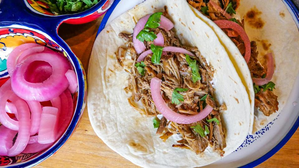 """<p>This simple slow cooker recipe makes enough to feed all of Congress. If you love <a href=""""https://www.thedailymeal.com/cook/ways-make-your-food-last-longer-gallery?referrer=yahoo&category=beauty_food&include_utm=1&utm_medium=referral&utm_source=yahoo&utm_campaign=feed"""" rel=""""nofollow noopener"""" target=""""_blank"""" data-ylk=""""slk:making your produce last longer"""" class=""""link rapid-noclick-resp"""">making your produce last longer</a> by pickling red onions, they'll go great on these tacos.</p> <p><a href=""""https://www.thedailymeal.com/recipes/easy-pork-carnita-tacos-recipe?referrer=yahoo&category=beauty_food&include_utm=1&utm_medium=referral&utm_source=yahoo&utm_campaign=feed"""" rel=""""nofollow noopener"""" target=""""_blank"""" data-ylk=""""slk:For the Carnitas Tacos recipe, click here."""" class=""""link rapid-noclick-resp"""">For the Carnitas Tacos recipe, click here.</a></p>"""