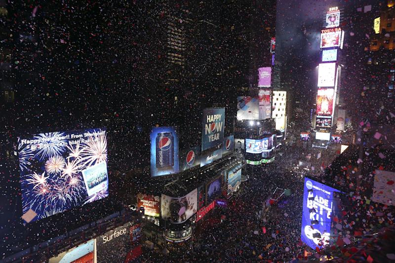 FILE - In this Jan. 1, 2013, file photo, donfetti flies over New York's Times Square after the clock strikes midnight during the New Year's Eve celebration as seen from the Marriott Marquis hotel in New York. As Americans prepare to ring in 2014, they look to the new year with an optimistic eye, according to a new AP-Times Square New Year's Eve poll, while their ratings of the year gone by are less than glowing. (AP Photo/Mary Altaffer, File)