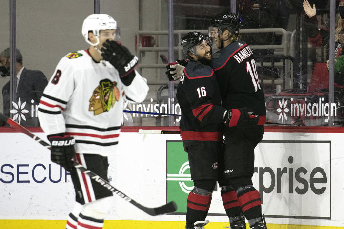 Carolina Hurricanes' Dougie Hamilton (19) celebrates his goal with teammate Vincent Trocheck (16) against the Chicago Blackhawks during the first period of an NHL hockey game in Raleigh, N.C., Monday, May 3, 2021. (AP Photo/Karl B DeBlaker)