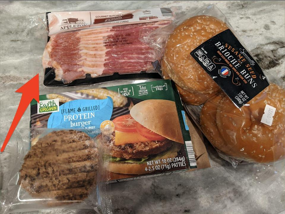 Aldi bacon, burgers, and buns on a granite counter, with a red arrow pointing to the bacon