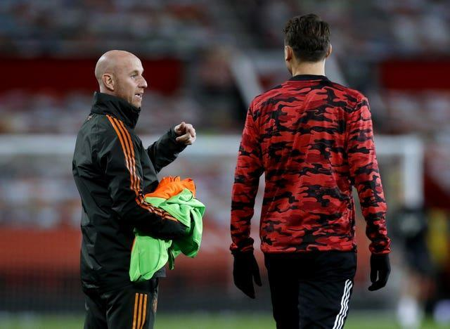 Manchester United first team development coach Nicky Butt (left) oversees the players warming up on the pitch ahead