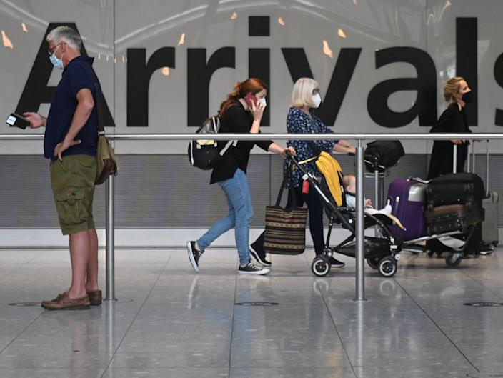 Passengers push their luggage on arrival in Terminal 5 at Heathrow airport in London, on June 3, 2021 (AFP via Getty Images)