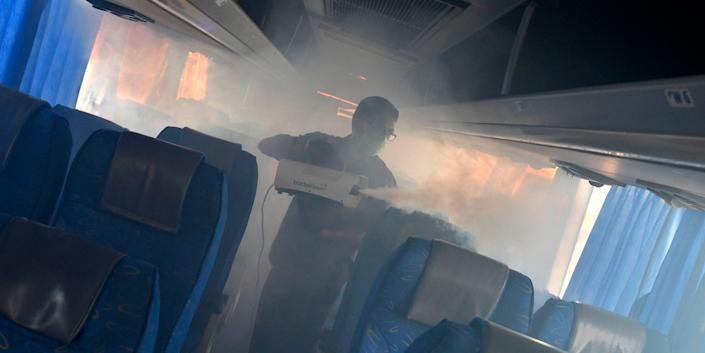 A worker fumigates the interiors of a Karnataka Interstate Transport bus to prevent the spread of the COVID-19 virus in Bangalore, India, on March 19, 2020.