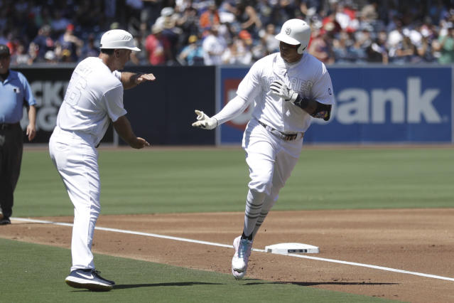 San Diego Padres' Manny Machado, right, reacts with third base coach Glenn Hoffman after hitting a two-run home run during the first inning of a baseball game against the Boston Red Sox Sunday, Aug. 25, 2019, in San Diego. (AP Photo/Gregory Bull)